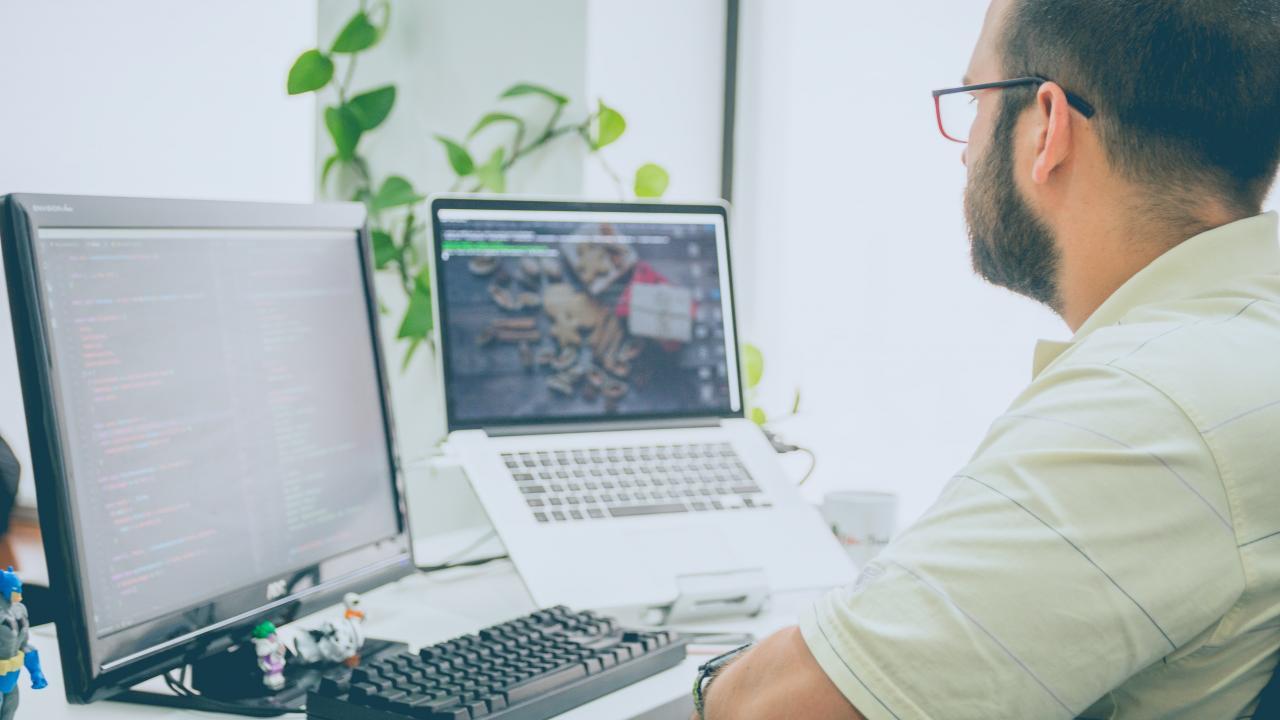 A man looking at laptop and monitor